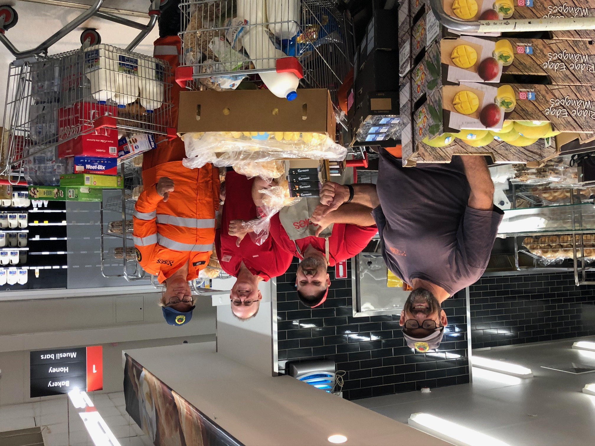 RFS fireys with Coles Batemans Bay team members receiving donations of full trolleys of groceries and fresh produce